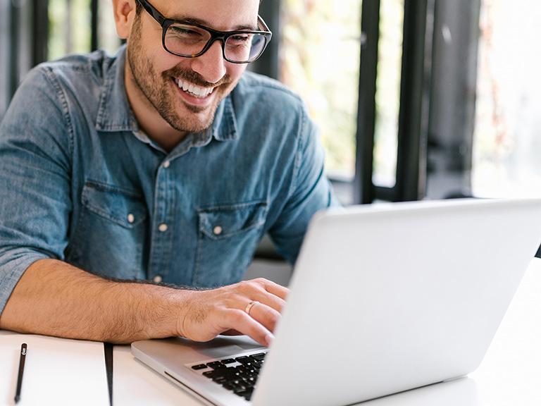usmiechnięty mężczyzna pisze nakomputerze